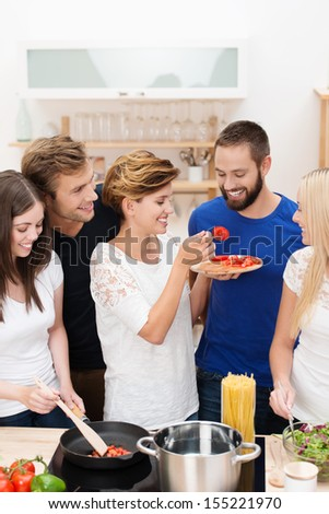 Diverse group of young friends cooking dinner together in the kitchen laughing as one man is tempted to try the recipe by a young woman - stock photo