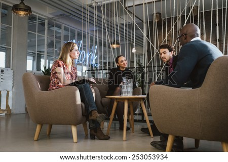 Diverse group of young people having a meeting in lobby. Young business executives meeting in office sharing creative ideas. - stock photo