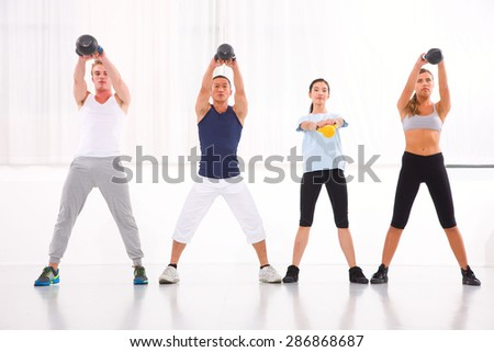 Diverse group practicing kettlebell exercise in crossfit gym