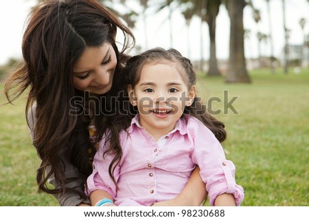 Diverse mom and daughter sitting in the grass - stock photo