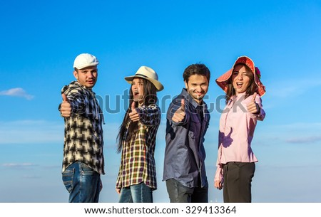 Diverse Multi-Ethnic Group of Young People Showing Thumbs Up Gesture Casual Relaxed Clothing Blue Sky Outdoor Background - stock photo