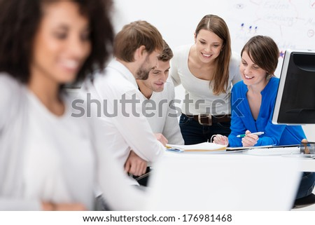 Diverse multiethnic group of young businesspeople in a meeting sitting at a table in the office discussing their business strategy and sharing information - stock photo