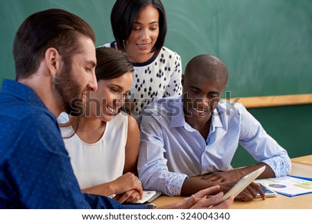 diverse multiracial colleagues discussing tech startup business ideas on tablet computer device - stock photo