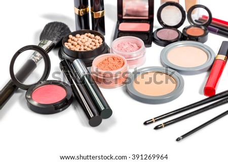 Diverse selection of brushes along side makeup powders, eye shadow, red and pink lipsticks and compact with foundation - stock photo