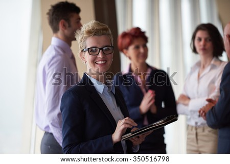 diverse startup business people group standing together as team  in modern bright office interior  with blonde  woman with glasses  in front as leader