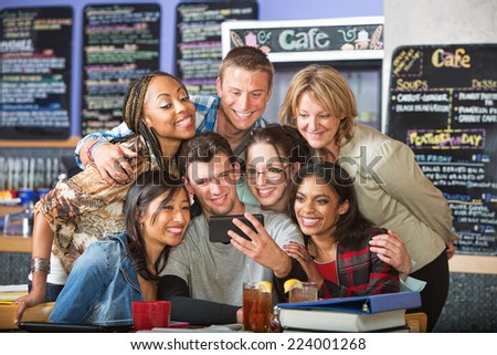 Diverse students smiling with camera phone in bistro - stock photo