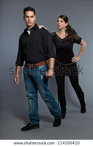 Diverse young couple together. Dressed in black. Studio shot. Isolated on grey background.
