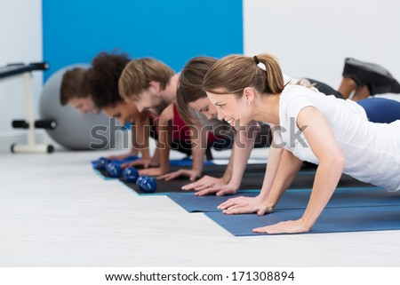Diverse young people working out in a gym together in a class doing push up in a healthy lifestyle and fitness concept - stock photo