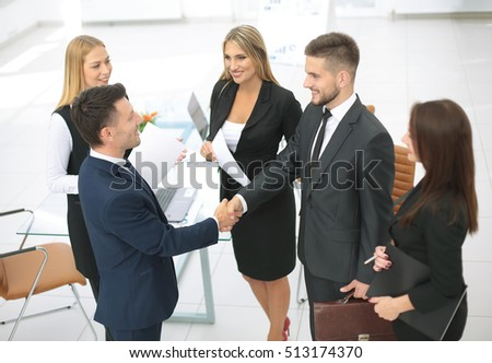 Diversity business team concluding contract with handshake in an