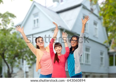 diversity, friendship and people concept - international group of happy smiling different women having fun over house background