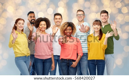 diversity, race, ethnicity and people concept - international group of happy smiling men and women waving hand over holidays lights background