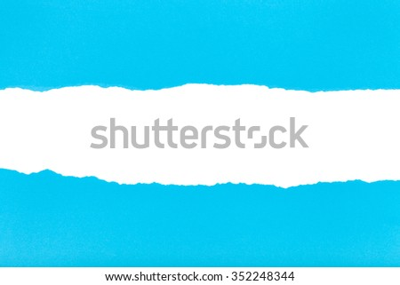 divided halves of the sheet of blue ripped paper on white background - stock photo