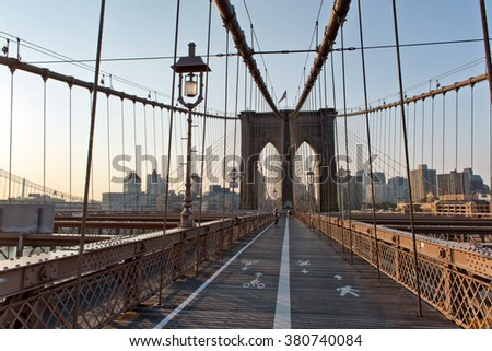 Divided Pedestrian Walkway Through Arches and Support Cables of Historic Brooklyn Bridge, an Iconic Tourist Destination and Landmark in New York City, New York, USA at Sunset