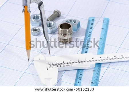 Divider, pencil, caliper, ruler and few screw nuts on graph paper background