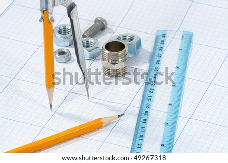 Divider, pencil, ruler and few screw nuts on graph paper background
