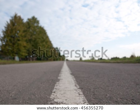 Dividing line on asphalt road goes into the distance. The view from ground level. The picture is blurred and not in focus. Can be used as background - stock photo