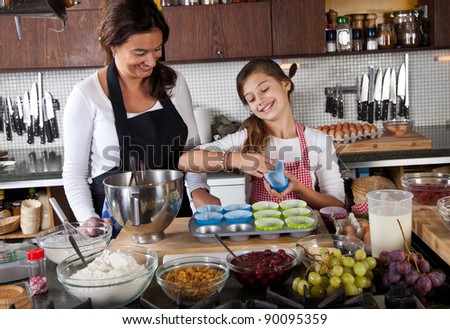 Dividing the cupcake papers over the tins - stock photo