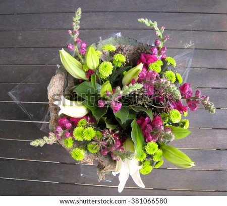 Divine Flower Arrangement Wrapped in Dried Lotus Leaves (Pink and Green Floral Arrangement) - stock photo