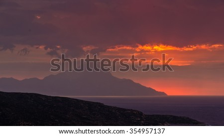 Divine light, stormy sky and sunrise on a landscape around holy mountain Athos in Greece