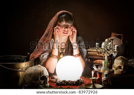 Diviner predicting the future with a crystal ball - stock photo