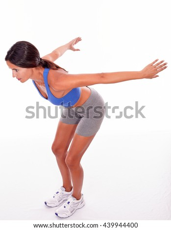 Diving brunette woman with hands and arms stretched behind while looking away wearing blue and grey casual clothing, isolated - stock photo