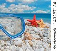 diving mask, starfish and necklace by the shore - stock photo