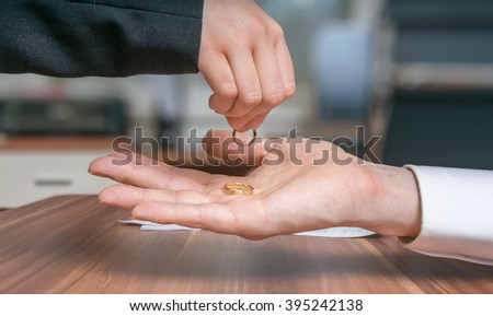 Divorce concept. Young couple is divorcing. Wife returns ring to her husband. - stock photo