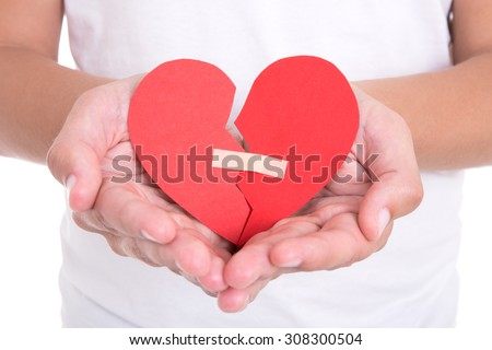divorce concept - young man holding broken heart with plaster - stock photo