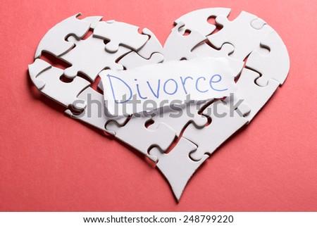 Divorce Label On Heart Shape Made Of Puzzle Over Orange Background - stock photo