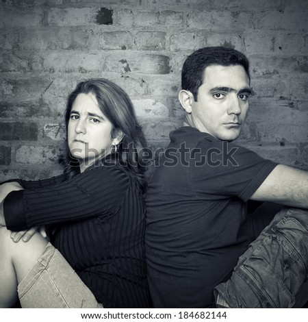 Divorce,problems - Young couple angry at each other sitting back to back with a bricks wall background - stock photo