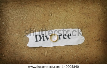Divorce text on ripped paper with gold wedding band - stock photo