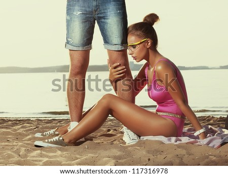 Divorcement, treason - disappointed young woman hugging men's legs - stock photo