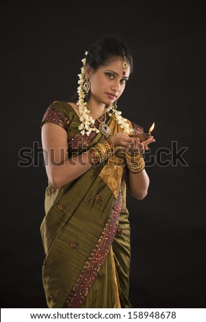 diwali or deepavali photo with female holding oil lamp during festival of light  - stock photo