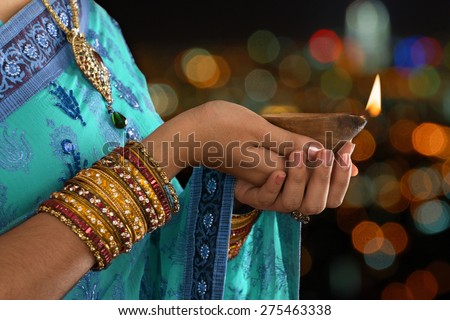 Diwali or festive of lights. Traditional Indian festival, woman in sari hands holding oil lamp, copy space at side. - stock photo