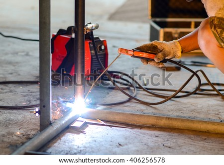 DIY, a Man welds two pieces of metal together at home - stock photo
