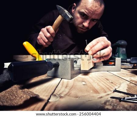 diy carpenter on duty dark background - stock photo