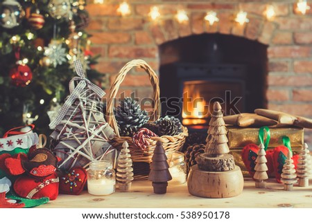 Diy Christmas: wooden toys made on wood lathe, handmade felt decorations, presents on the table, Christmas tree and fireplace with burning fire on the background, selective focus, toned photo