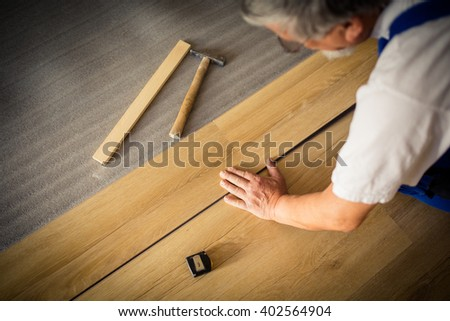 DIY, repair, building and home concept - close up of male hands lying parquet floor board/laminate flooring (shallow DOF; color toned image)