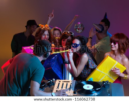 dj and group of beautiful girls leaning towards each other, at party, the girls holding colored wrapped presents and blowing party horns - stock photo