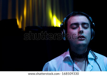 DJ at a party listening to the music on his headphones with his eyes closed as he enjoys the rythm and beat of the music he has mixed with colourful lighting in the darkness behind him - stock photo