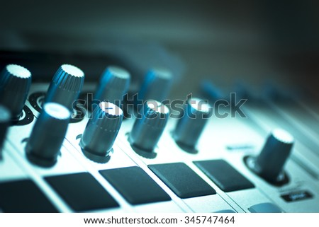 DJ console cd mp4 deejay mixing desk buttons and knobs in Ibiza house techno dance music wedding reception party in nightclub with colored lighting effect disco lights. - stock photo