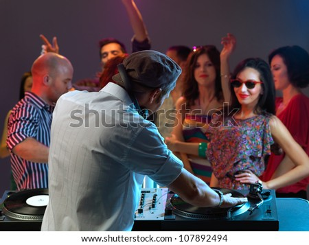 dj entertaining the happy, dancing crowd in a night club - stock photo