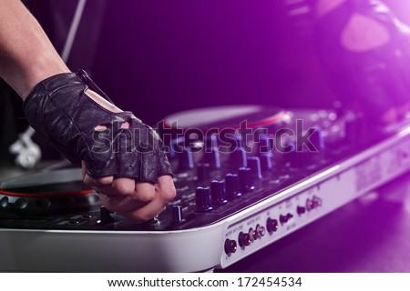 Dj hands on equipment deck - stock photo