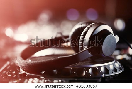 DJ headphones laying on digital CD turntable music player. Top level audio equipment for studio,event,concert. Widely used by professional disc jockey. Macro, close up