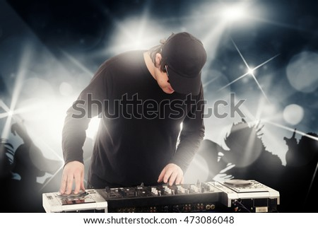 DJ in cap makes music on the mixer