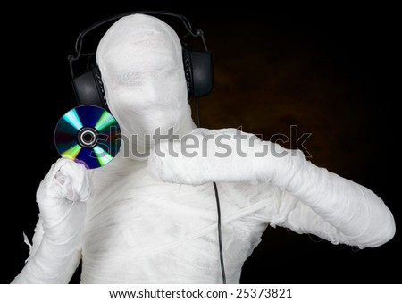 DJ in costume mummy with ear-phones and disc on black