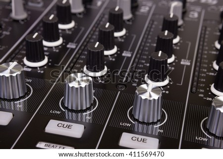 DJ mixer ?? controller. Knobs and switches of black audio mixing console in nightclub. Selective focus. - stock photo