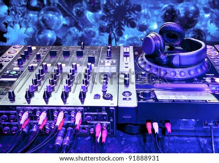 Dj mixer with headphones at a nightclub. Festive background in the New Year Eve