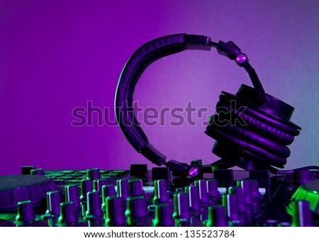 Dj mixer with headphones at night club - stock photo