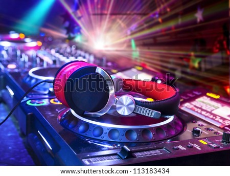 Dj mixer with headphones at nightclub.  In the background laser light show - stock photo